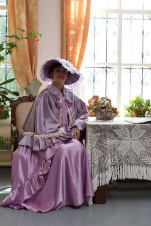 historical periods: The woman poses in a lilac dress Stock Photo
