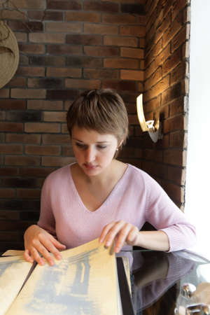 Young woman in restaurant reading a menu photo