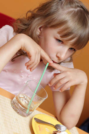 A sad little girl drinks water in cafe photo