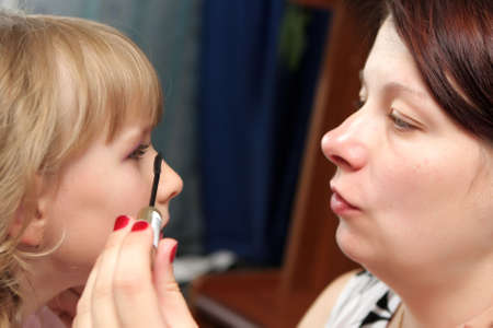 A mother applying make up to daughter photo