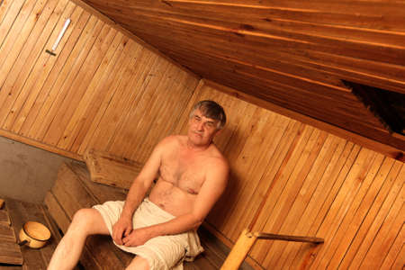 The mature man poses in a sauna photo
