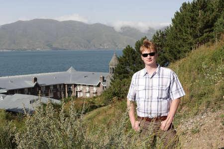 The tourist poses on the monastery background, Armenia photo