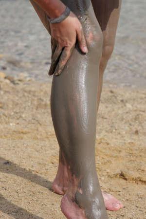 A woman is applying mineral mud on legs, dead sea photo