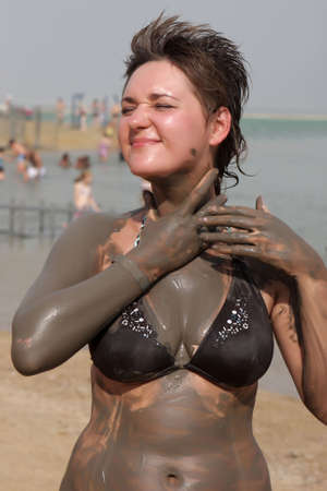 The girl is applying mineral mad on dead sea, Israel photo