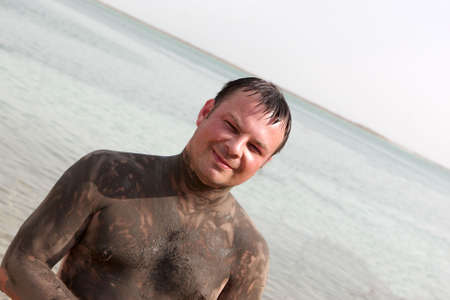 The man shows Mineral mud body on a beach of Dead sea photo