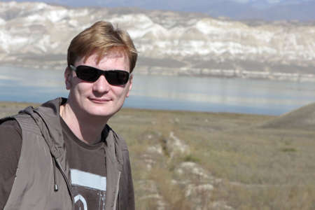 Portrait of man on Toktogul Reservoir background, located in the Jalal-Abad Province of Kyrgyzstan, is the largest of the reservoirs on the path of the Naryn River. Bishkek - Osh road photo