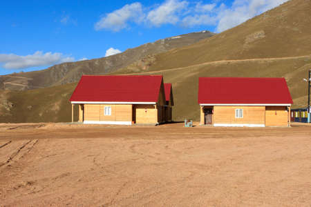 kirgizia: The two wooden houses at the foot of a hill, Kyrgyzstan (Bishkek - Osh road) Stock Photo