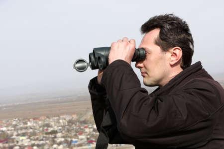 The man looks through binoculars in spring Stock Photo - 6678897