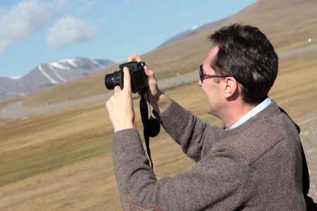The man takes a picture of landscape in Kyrgyzstan Stock Photo - 6678881
