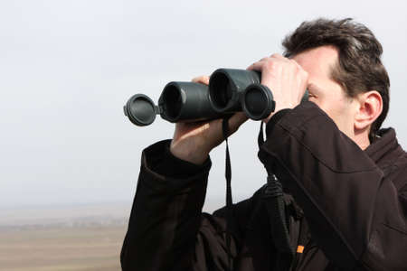 The man looks through a binoculars in spring Stock Photo - 6678902