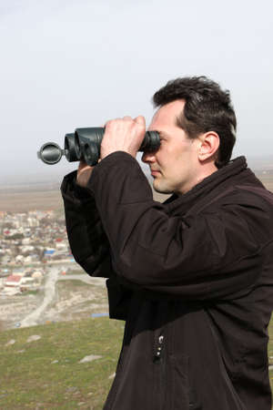 The man looks through a binoculars, Kyrgyzstan Stock Photo - 6678909
