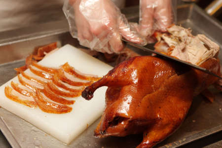 Chinese cook prepares Peking Roast Duck. Peking Duck is a famous duck dish from Beijing that has been prepared since the imperial era, and is now considered one of Chinas national foods. photo