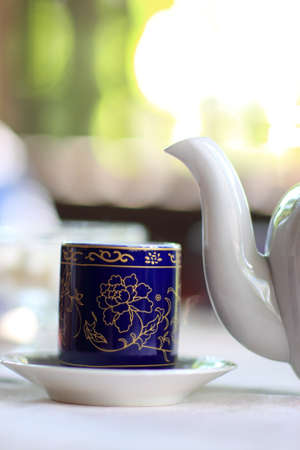 Cup of tea and spout of teapot photo