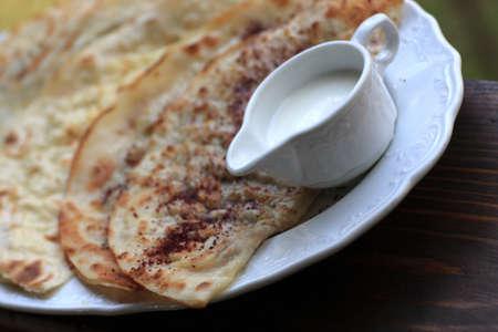 azerbaijani: Cuisine of Azerbaijan - Kutaby with white sauceboat Stock Photo