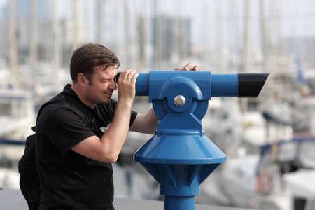 The man looks through telescope on city photo