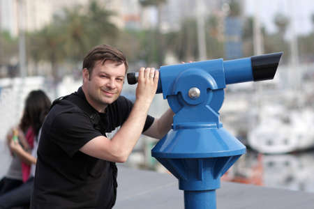 The man poses with telescope at summer photo