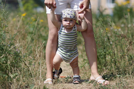 The mother learns her baby to walk outdoor photo