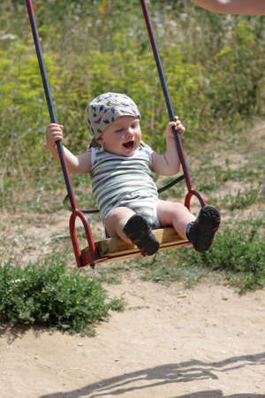 The happy baby is swinging by swing