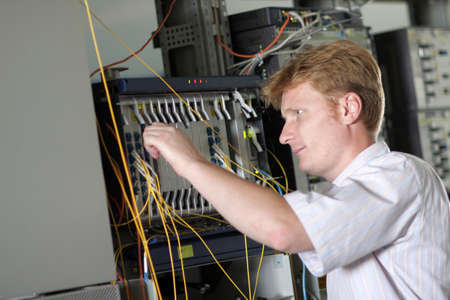 The telecom engineer adjusts multiplexer on communications center