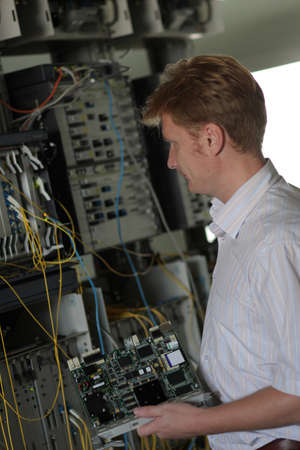 The engineer changes board of multiplexer on communications center Stock Photo