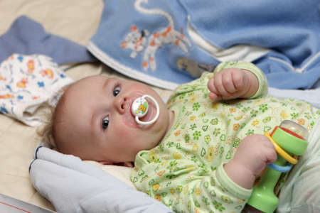 The baby holds a rattle on the bed at home photo
