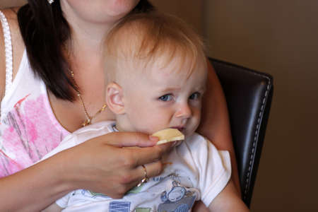 The baby not eating cheese from hands of mother Stock Photo