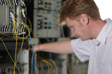 The telecom engineer looks on the multiplexer photo