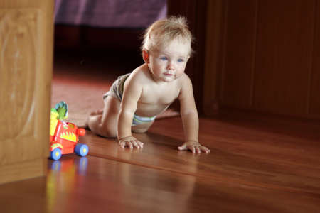 The baby creeps on floor at home Stock Photo