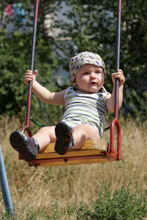 Portrait of the swinging baby at park
