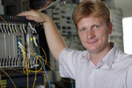 Die Telecom-Ingenieur-Posen auf einem multiplexer Hintergrund Standard-Bild - 7488782