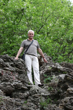 The mature man poses on a hill in the forest Stock Photo - 7491484