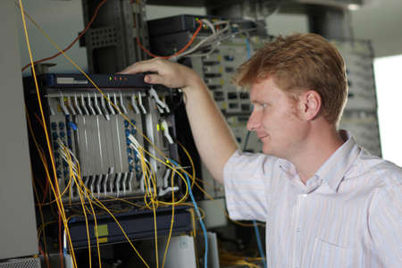 The telecom engineer looks on the multiplexer on communication site