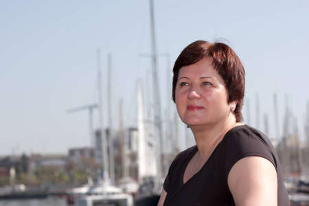 Mature woman poses on a harbor background, Barcelona photo