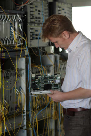 The telecom engineer changes card on a multiplexer