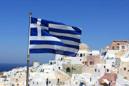 Greece flag on Oia background at Santorini island. It is town remains one of the foremost tourist attractions of the Aegean Sea.