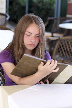 The teen reads a menu in the cafe photo