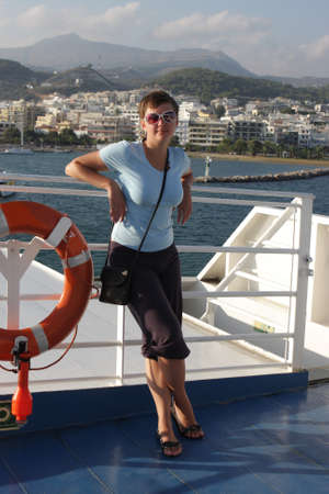 hovercraft: Woman poses at upper deck of hovercraft on Retimo background, Crete Stock Photo