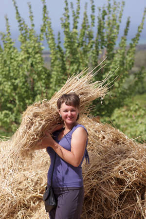 armful: The woman holds armful of wheat, greece