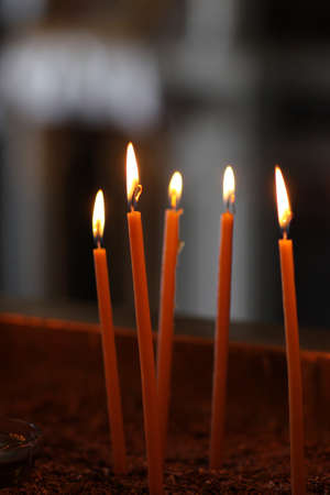 The burning votive candles in greek church