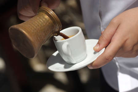 Waiter is pouring coffee at the restaurant photo