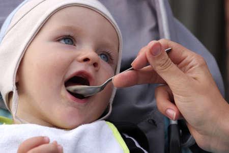 The funny baby is eating milk porridge photo