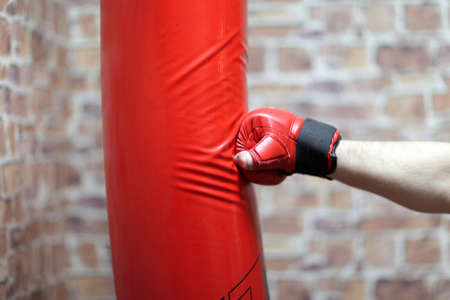 Boxing training - hand and red punching bag Stock Photo