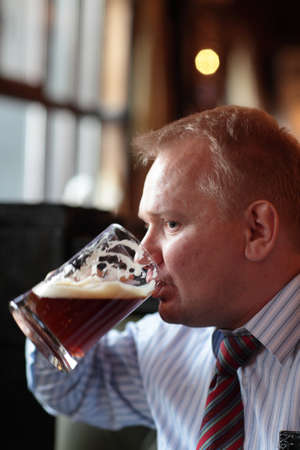 necktie and beer: The man drinks beer in the pub Stock Photo