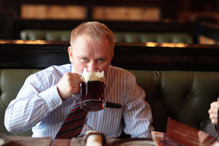 beer and necktie: The man drinks brown ale in the pub