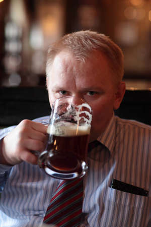 necktie beer: The man poses with glass of beer in the pub