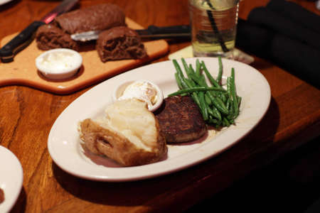 It is filet mignon with potato and pea pods photo