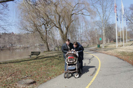 The couple look at baby in carriage photo