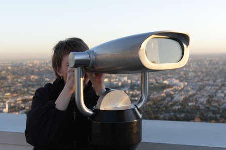 The woman looks through the binoculars on Los Angeles, USA photo