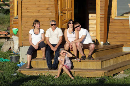 The family sit on the wooden porch photo