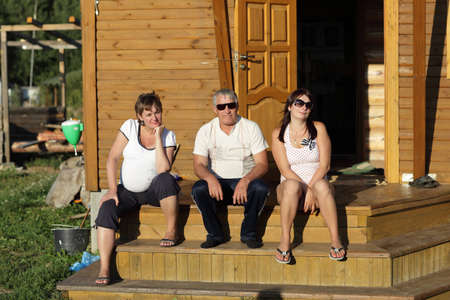 The family pose on the wooden porch  photo